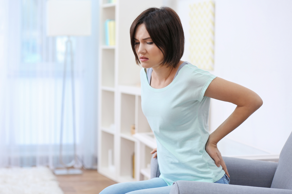 woman suffering from lower back pain and is in need of chiropractic care